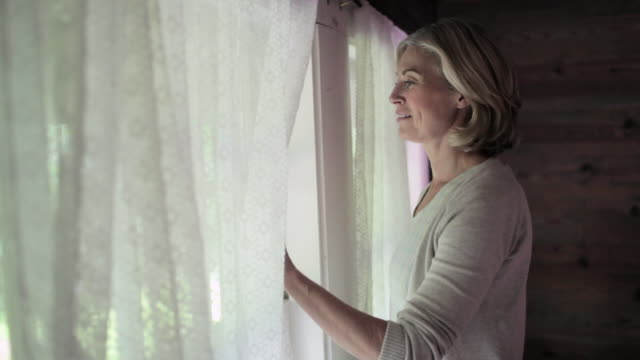 mature woman looking out of window - in den vierzigern stock-videos und b-roll-filmmaterial