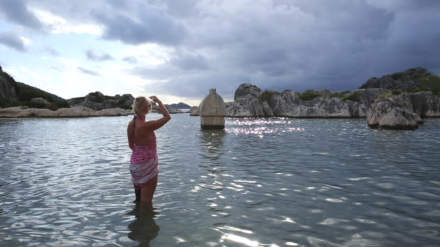 vídeos de stock e filmes b-roll de mature woman looks out to a partially sunken sarcophagus - só uma mulher madura