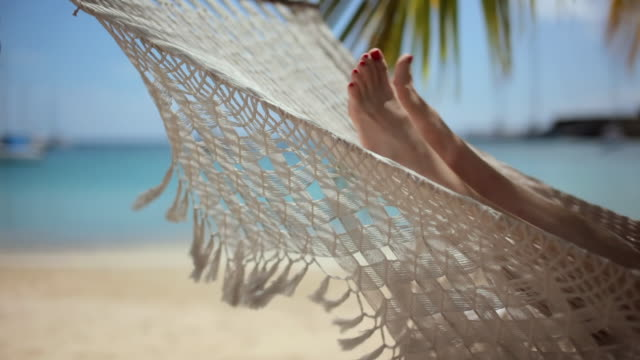 ms mature woman lying in hammock on beach / english harbor, antigua and barbuda - karibik stock-videos und b-roll-filmmaterial