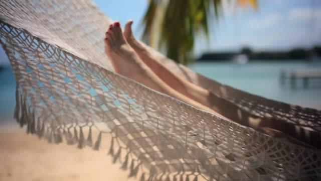 ms mature woman lying in hammock on beach / english harbor, antigua and barbuda - hammock stock videos & royalty-free footage