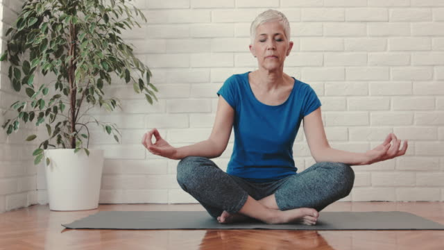 mature woman meditating in lotus position with her eyes closed. - home workout stock videos & royalty-free footage