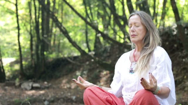 mature woman meditating in nature - one senior woman only stock videos & royalty-free footage