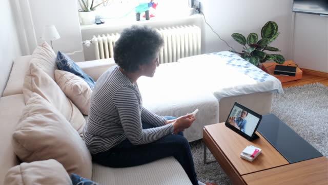 vídeos y material grabado en eventos de stock de mujer madura en una videotelemedicina con un médico en casa - médico de cabecera