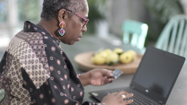 A mature woman on her lap top using her credit card.