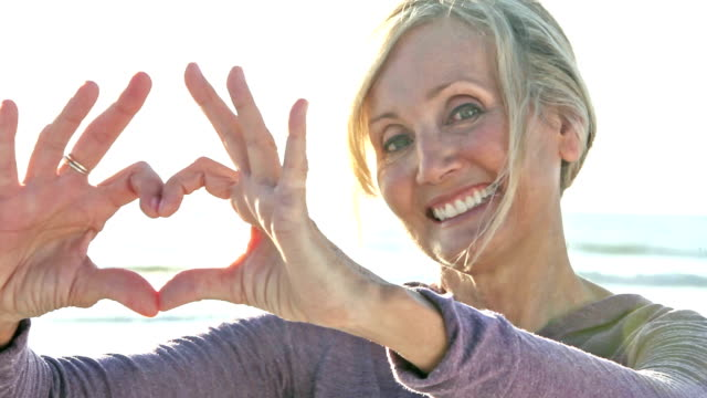 Mature woman on sunny beach makes heart shape with hands