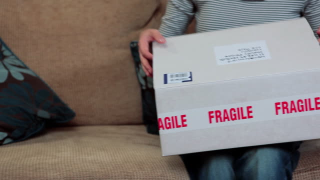 mature woman opening parcel containing glass vase - frauen über 40 stock-videos und b-roll-filmmaterial