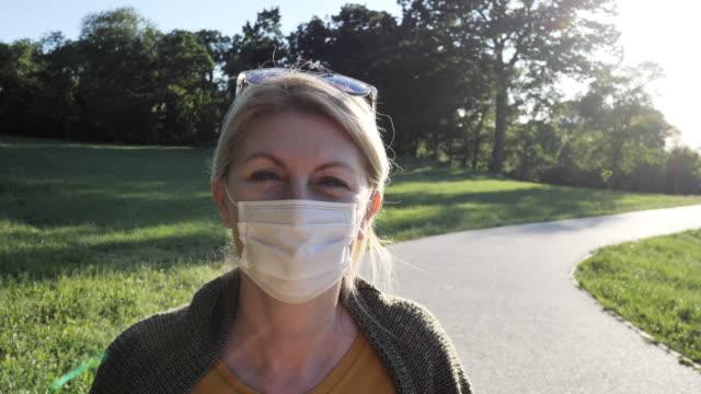 成熟した女性は、上のフェイスマスクで社会的な距離を保つ、春の日に屋外で - 老化点の映像素材/bロール