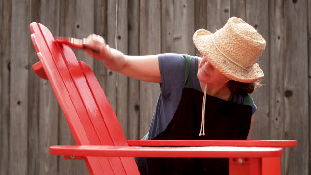 mature woman painting a beach chair at her backyard - fence stock videos & royalty-free footage