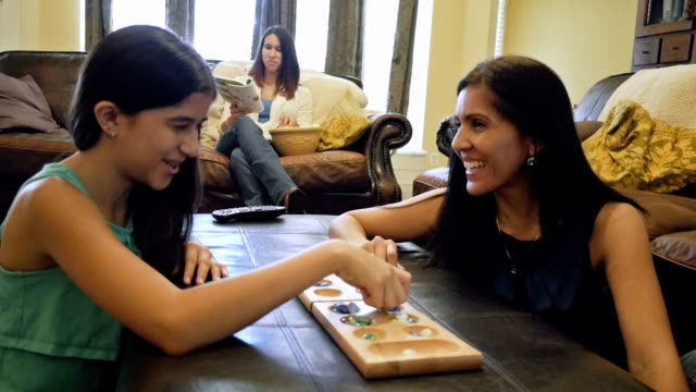Mature woman playing board game with preteen daughter at home