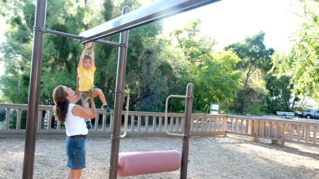 vídeos de stock, filmes e b-roll de mulher madura que joga com seu filho no parque - calção