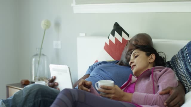 vídeos de stock, filmes e b-roll de mature woman pointing at device screen while lying in bed - caneca