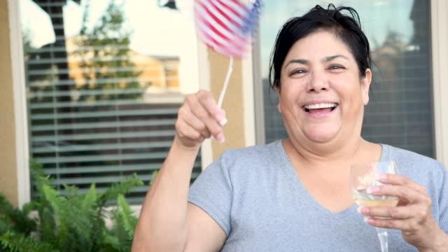 mature woman posing looking at the camera waving a us flag - brown hair stock videos & royalty-free footage