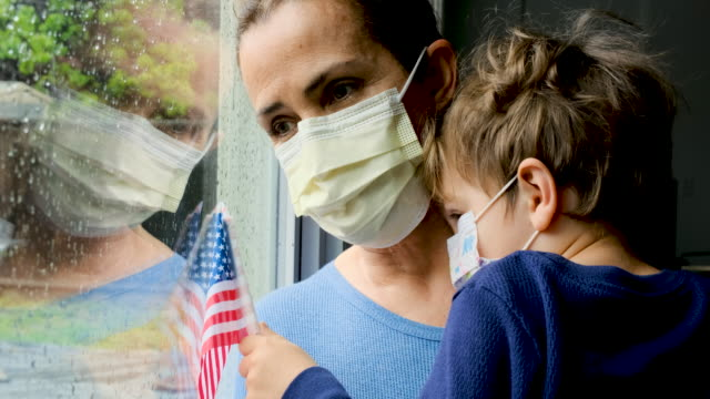 mature woman posing with her son, both with protective masks, very sad looking through window worried about covid-19 lockdown - unemployment stock videos & royalty-free footage