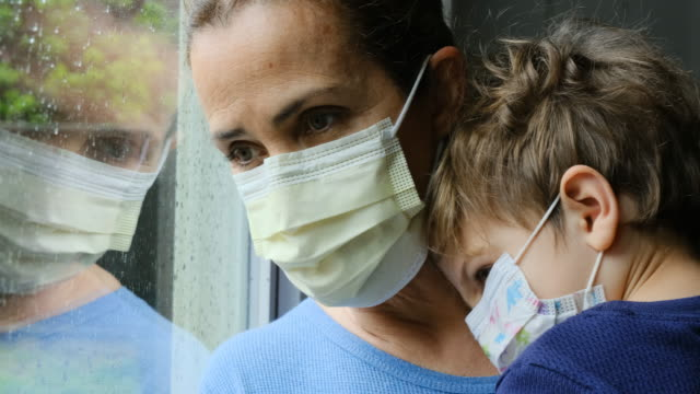 mature woman posing with her son, both with protective masks, very sad looking through window worried about covid-19 lockdown - quarantena video stock e b–roll