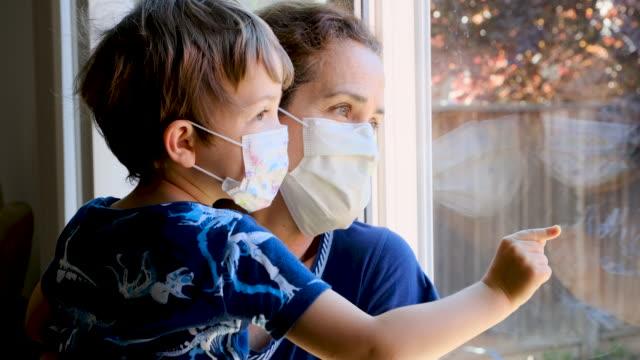 vidéos et rushes de femme mûr posant avec son fils, tous deux avec des masques protecteurs, très triste regardant par la fenêtre s'inquiète au sujet de covid-19 verrouillage - quadragénaire