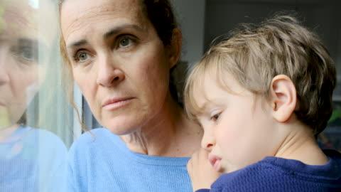 vídeos y material grabado en eventos de stock de mujer madura posando con su hijo, muy triste mirando a través de la ventana preocupado por covid-19 encierro - preocupado