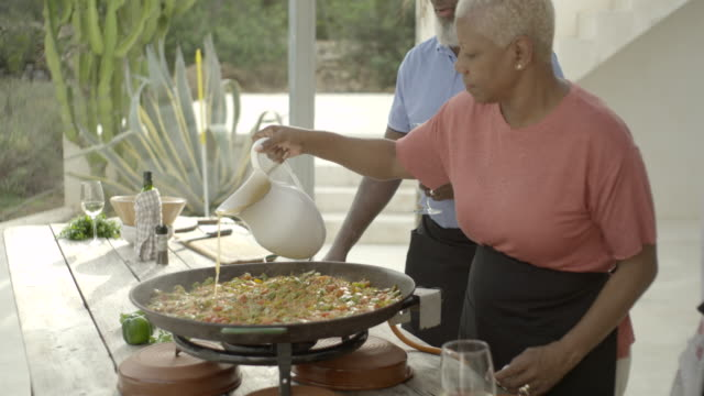 mature woman pours stock into paella pan (wide) - african ethnicity stock videos & royalty-free footage