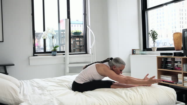 Mature woman practicing yoga on bed