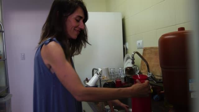 vídeos de stock e filmes b-roll de mature woman preparing coffee in the kitchen - pequeno
