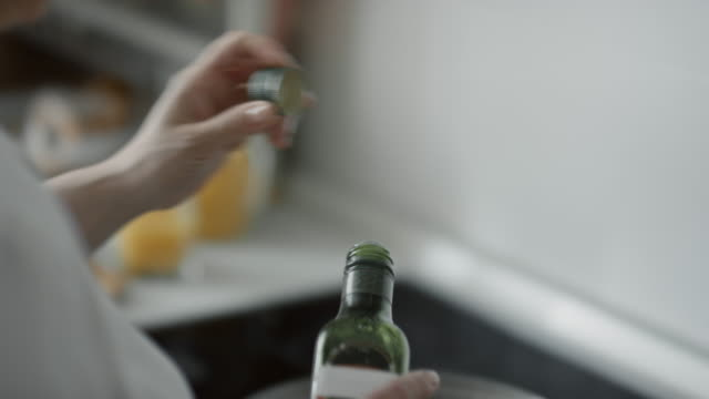 mature woman preparing to make fried eggs for breakfast - ストーブ点の映像素材/bロール