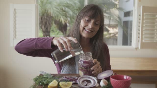 mature woman preserving vegetables at home - 缶詰にする点の映像素材/bロール