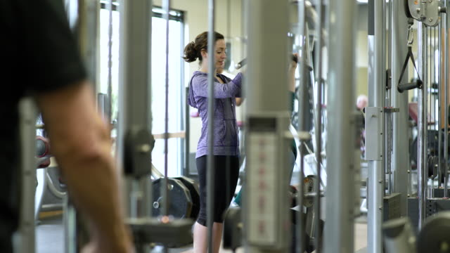 Mature woman pulldown exercising with a trainer