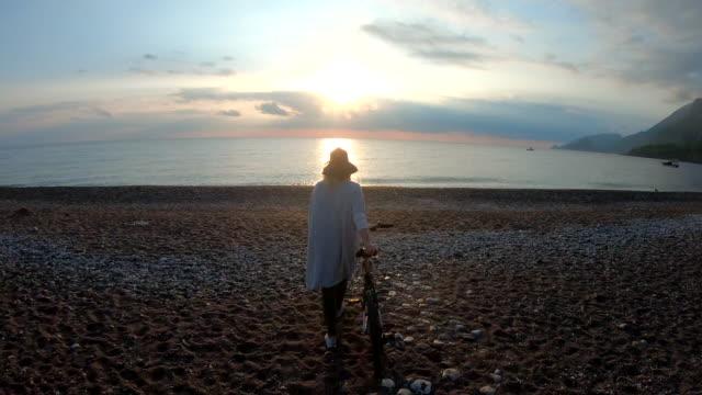 vídeos de stock e filmes b-roll de mature woman pushes bike across beach at sunrise - plano charriot