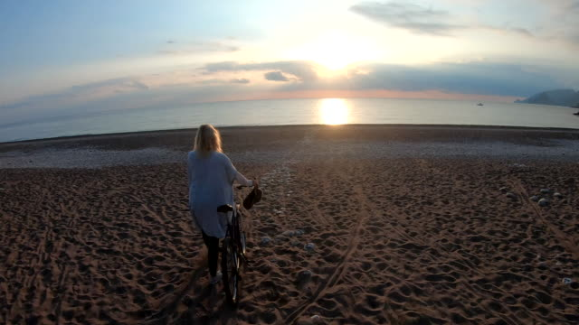 mature woman pushes bike across beach at sunrise - beach holiday stock videos & royalty-free footage