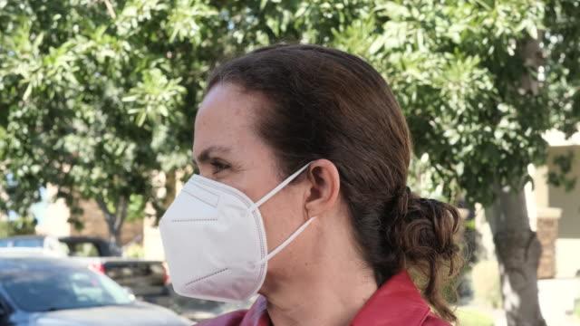vidéos et rushes de femme mûre mise dedans sur un masque protecteur de visage de n95 - porter