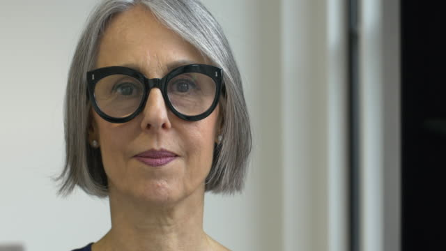mature woman putting on spectacles - capelli grigi video stock e b–roll
