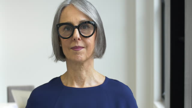 Mature woman putting on spectacles