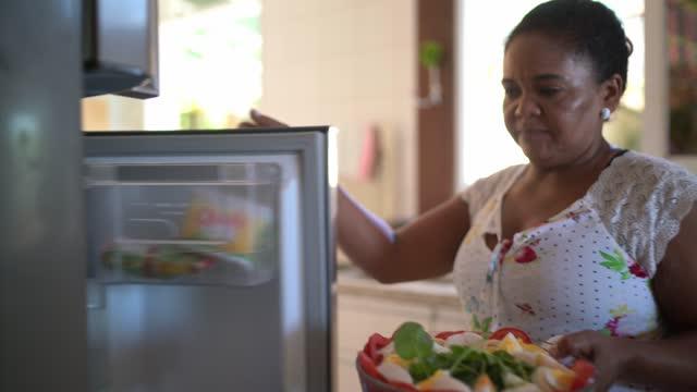 vidéos et rushes de femme mûr mettant le saladier dans le réfrigérateur à la maison - organisation