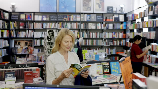 mature woman reading a book in bookstore - book shop stock videos & royalty-free footage