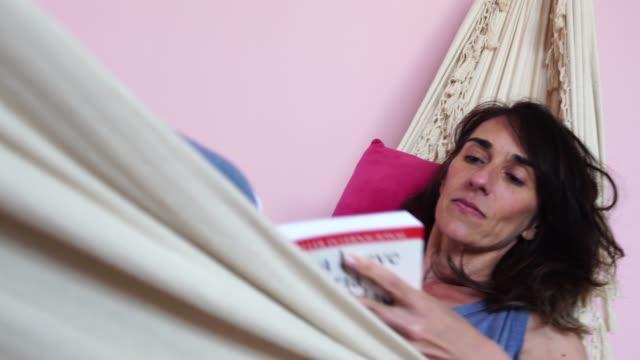 vídeos de stock, filmes e b-roll de mulher madura, lendo um livro na rede em casa - rede de dormir
