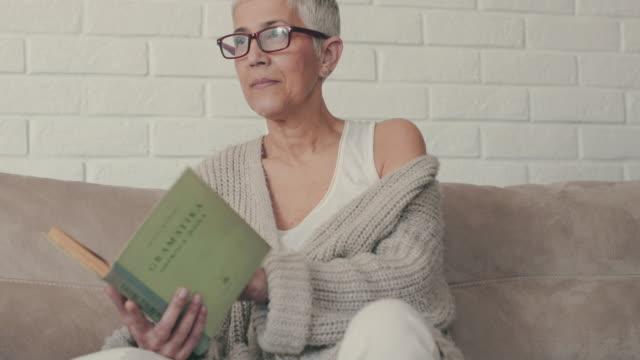 vídeos y material grabado en eventos de stock de mujer madura leyendo una novela mientras se relaja en el sofá. - leer