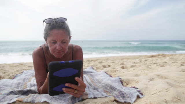 mature woman reading on tablet laying at the beach in the south of france. - towel stock videos & royalty-free footage