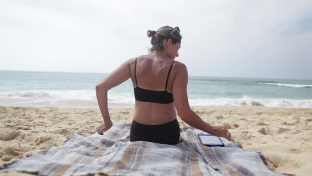 mature woman reading on tablet sitting at the beach in the south of france. - asciugamano video stock e b–roll
