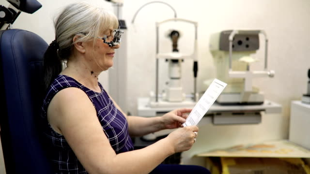 mature woman reading text during eye exam - lens optical instrument stock videos & royalty-free footage