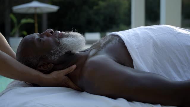 vídeos de stock e filmes b-roll de mature woman receives neck and shoulder massage - massagem