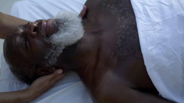 mature woman receives neck massage - masseur stock videos & royalty-free footage