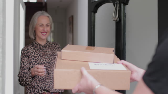 vídeos de stock, filmes e b-roll de mature woman receiving a home delivery - entregador