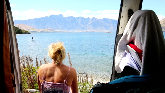 mature woman relaxes in camper-van on a lakeshore - one mature woman only stock videos & royalty-free footage