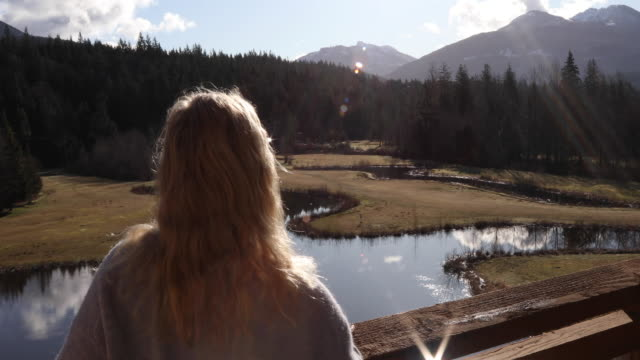 mature woman relaxes on deck overlooking pond, mountains - pond stock videos & royalty-free footage