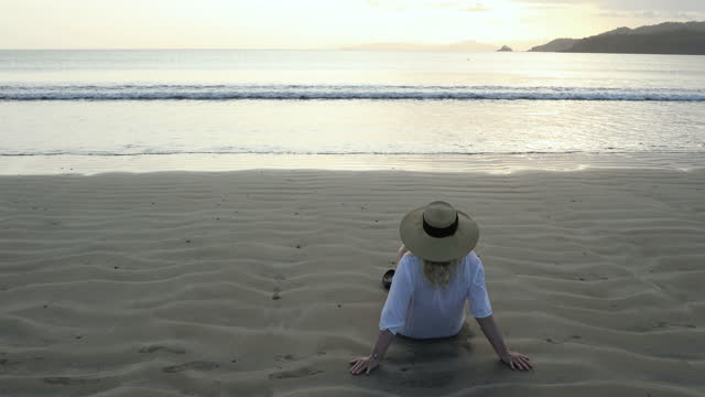mature woman relaxes on empty beach, at sunrise - rear view stock videos & royalty-free footage