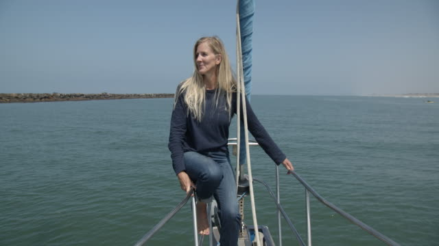 mature woman relaxing on a sailboat - nautical vessel video stock e b–roll