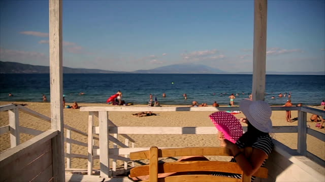 mature woman relaxing on the beach - hand fan stock videos and b-roll footage