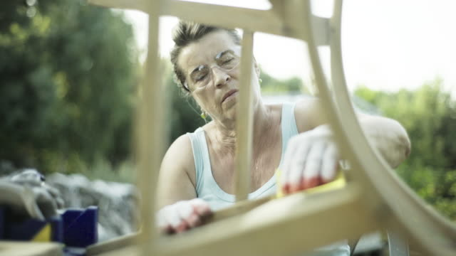 Mature woman renovate old furniture
