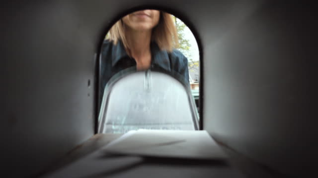 cu mature woman retrieves mail from mailbox / neenah, wisconsin, usa  - mailbox stock videos and b-roll footage