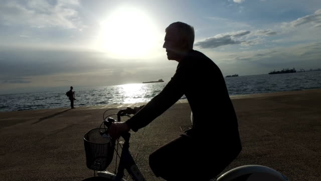 mature woman rides a bicycle by the sea at sunset - thessalonika stock videos & royalty-free footage