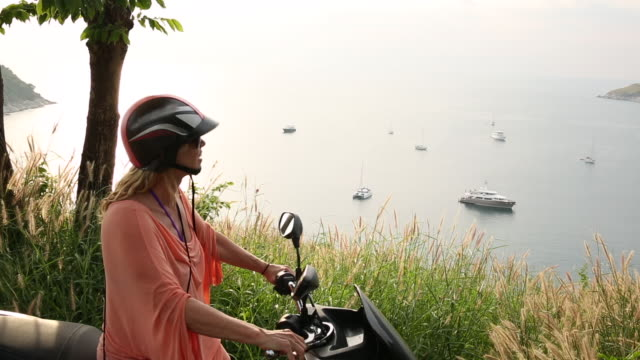 mature woman rides scooter to viewpoint above sea - moped stock videos and b-roll footage